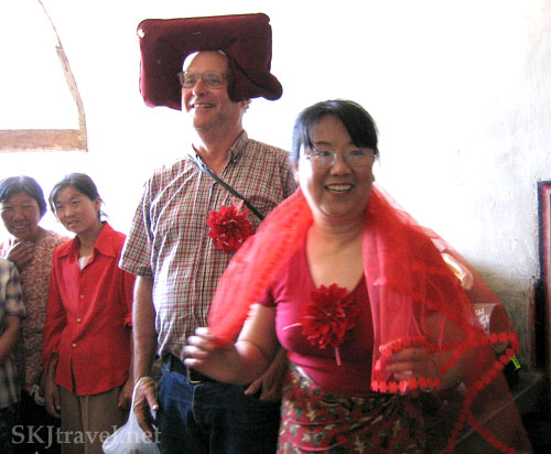 American man and Chinese woman dressed in red to perform a mock wedding ceremony in Shaanxi Province, China. Photo by Shara Johnson