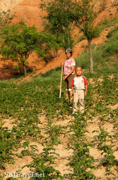 Peasant woman and her toddler son standing in their cropfield, she with a hoe, in a village in Shaanxi Province, China. Photo by Shara Johnson