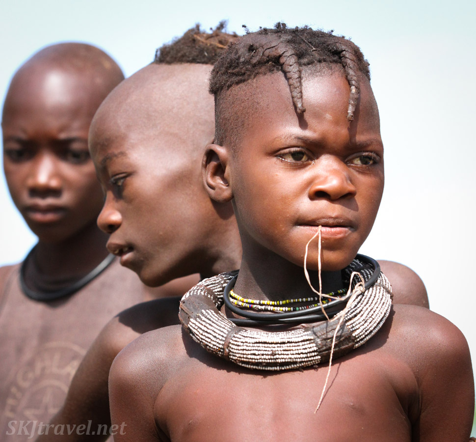 Three Himba adolescents, a girl and two boys. Kunene region of Kaokoland, Namibia.