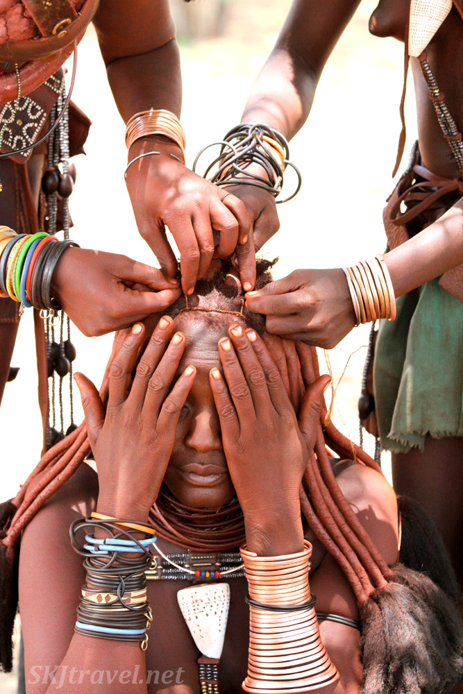 Two Himba women working on another's hair. Kunene region of Kaokoland, Namibia.