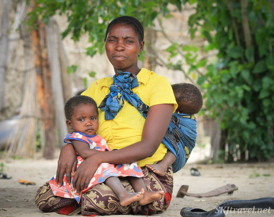 Mother with a toddler and infant, colorful clothes, Kavango region of Namibia.