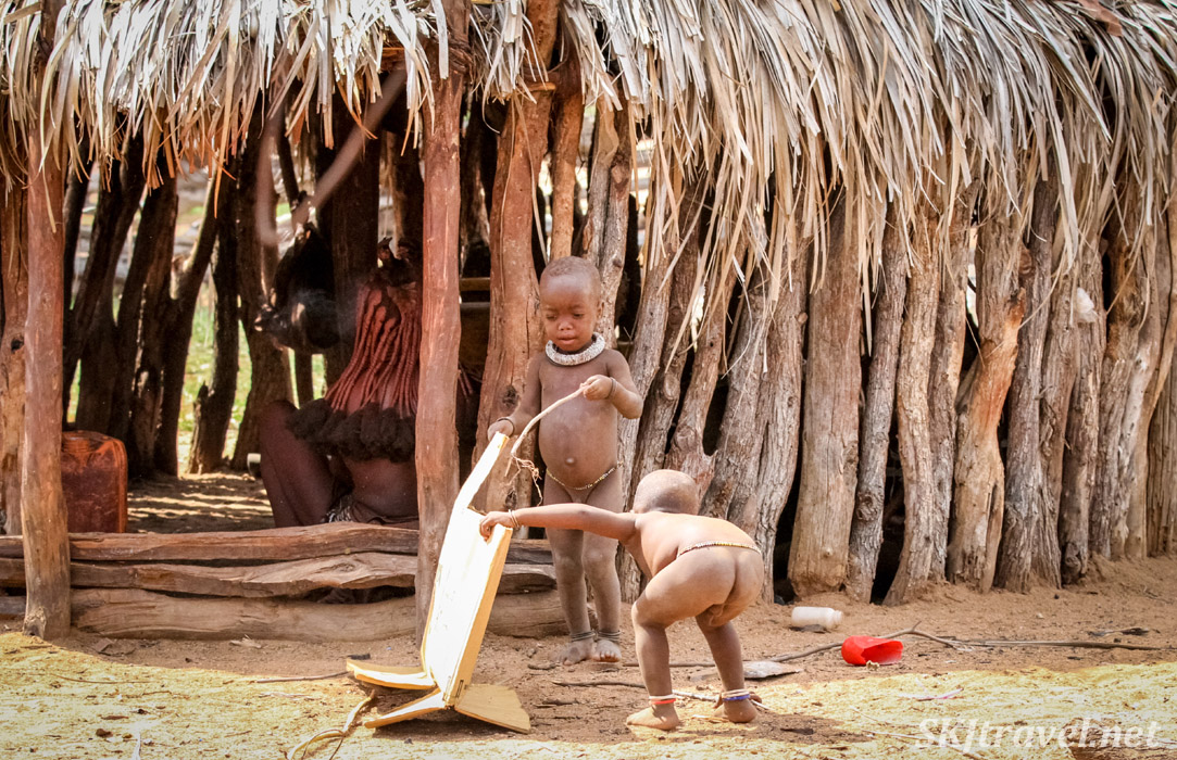Two young Himba kids playing with a cardboard box. Kunene region of Kaokoland, Nambia.