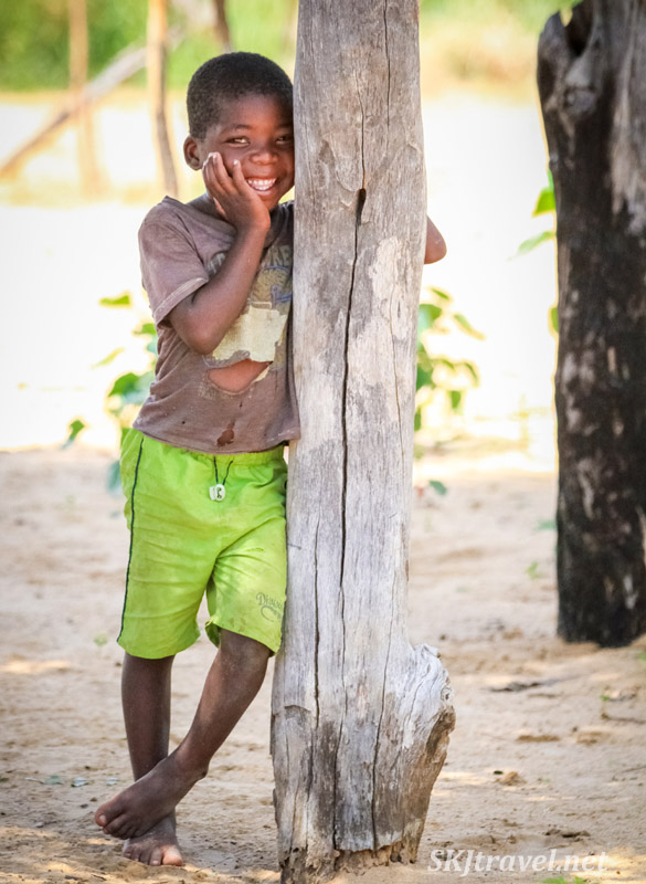 Shy boy smiling beside a post. Caprivi Strip, Namibia.