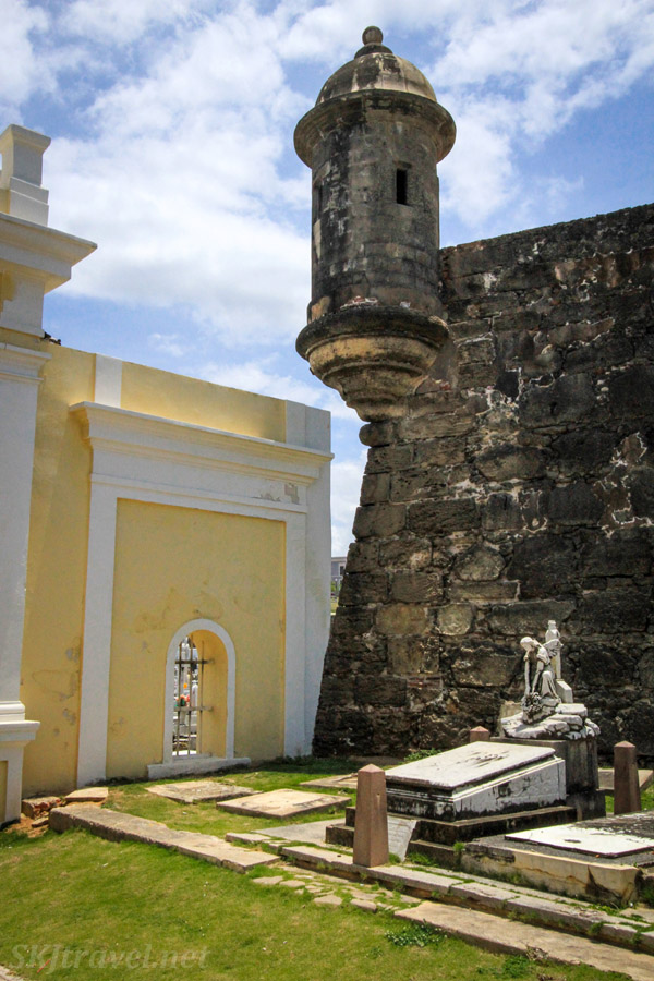 Yellow archway and tombstones inside Santa Maria Magdalena de Pazzis Cemetery, directly below the fortress wall of Castillo San Felipe del Morro and right on the ocean shore. Old San Juan, Puerto Rico.