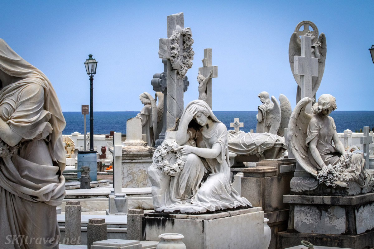 Angels, crosses, weeping women statues on the graves in Santa Maria Magdalena de Pazzis Cemetery, against the backdrop of the ocean, Old San Juan, Puerto Rico.