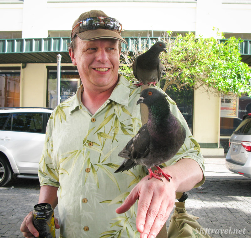 Erik hosting pigeons on his shoulder and arm at a square in Old San Juan, Puerto Rico.
