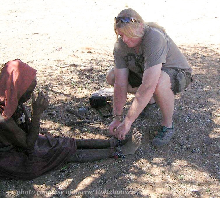 Cutting the chains off of Ndjinaa's ankles. December 12, 2012. Near Epupa Falls, Namibia.