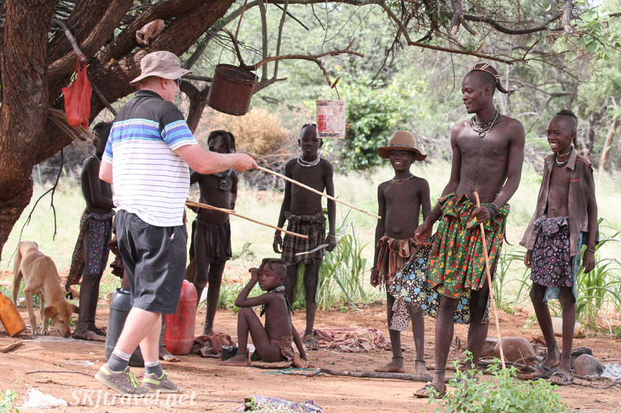 Berrie and young Himba man preparing to square off in a stick-fighting duel. Namibia.