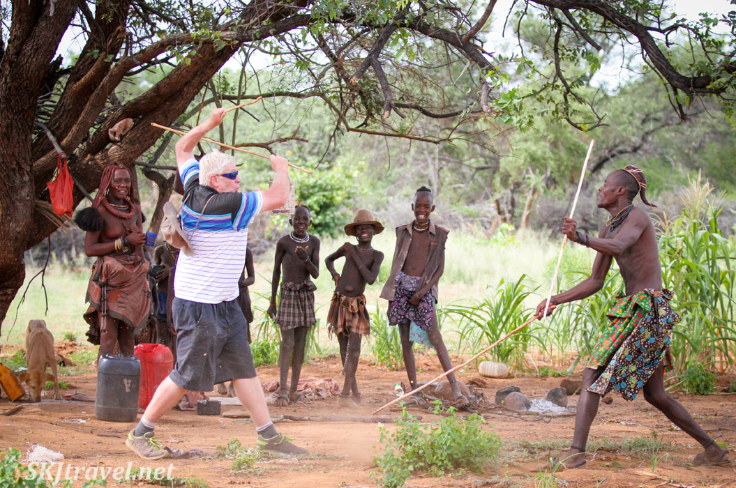 White man versus Himba ... a stick fighting duel! Near Epupa Falls, Namibia.