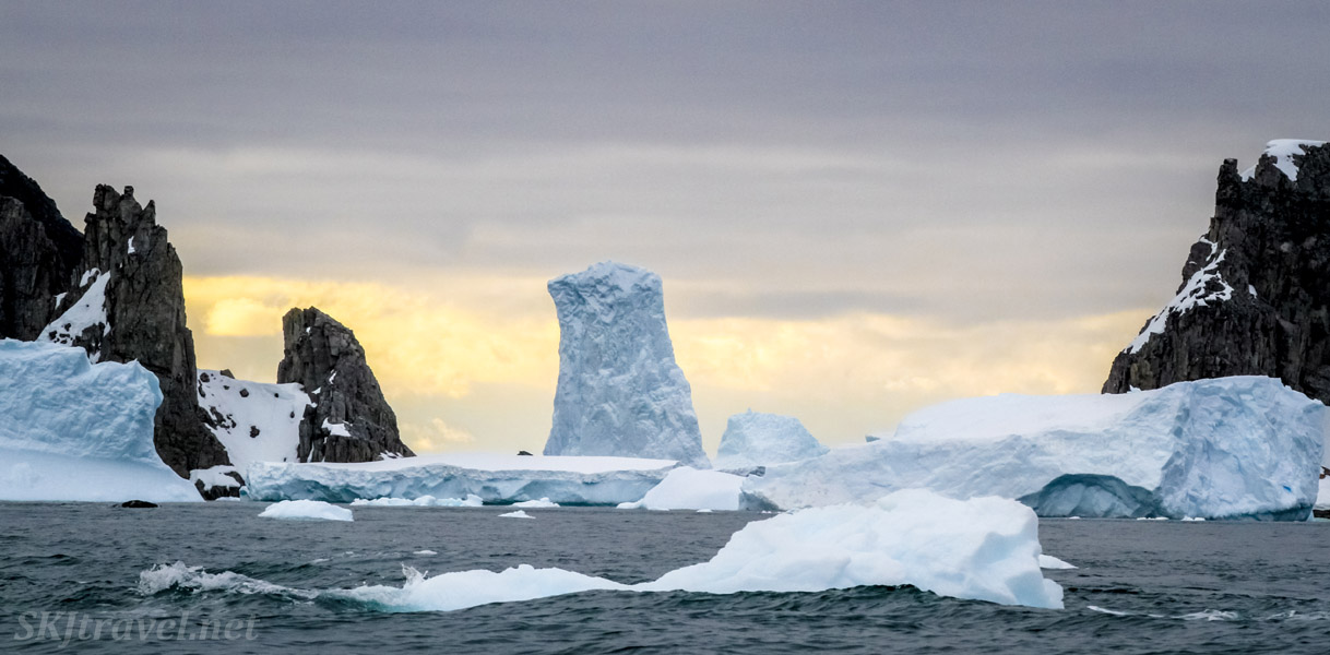 Rocks and icebergs with a pastel sky at Spert Island, Antarctica.