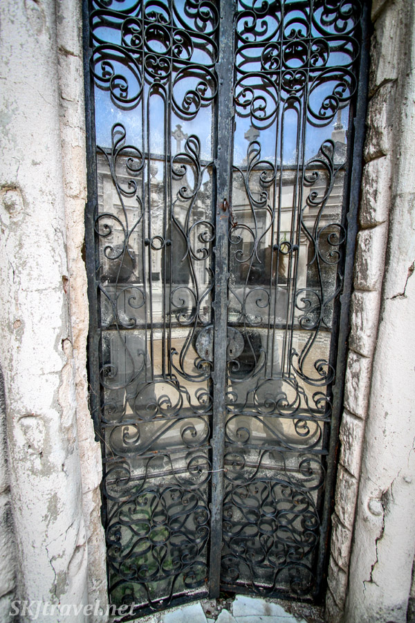 Door to a mausoleum with reflections in the glass, Recoleta Cemetery, Buenos Aires, Argentina.