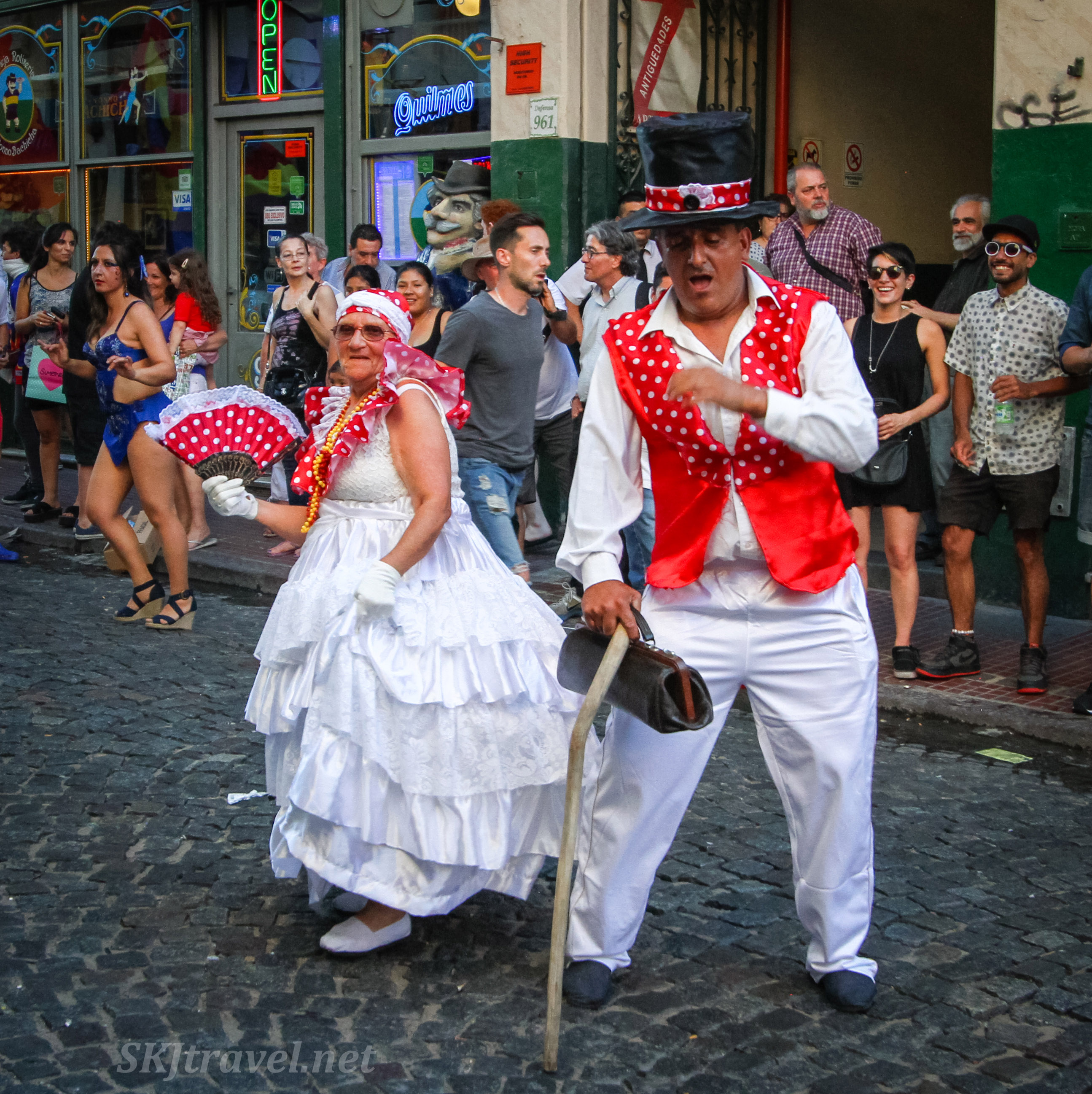 Mama Vieja and Gramillero characters dancing and play acting in the San Telmo Candombe parade, Buenos Aires, Argentina.