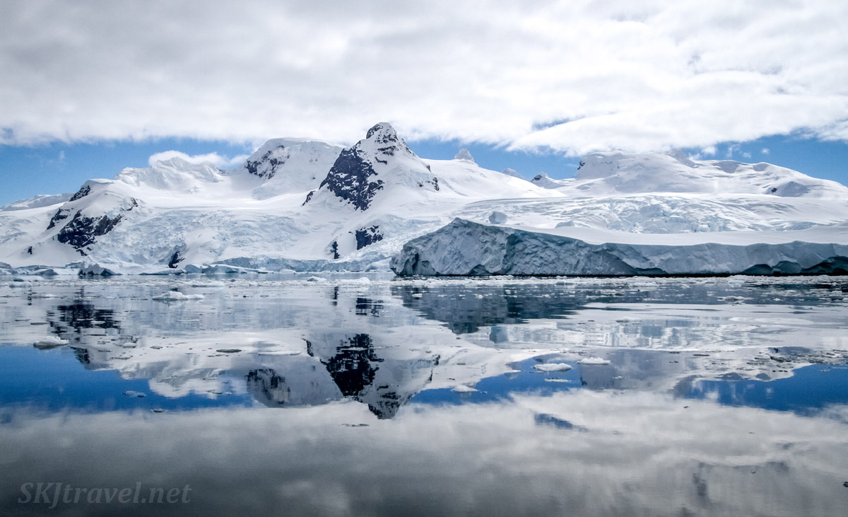 Snow covered landscape reflected in the bright blue waters of Cierva Cove, Antarctica.