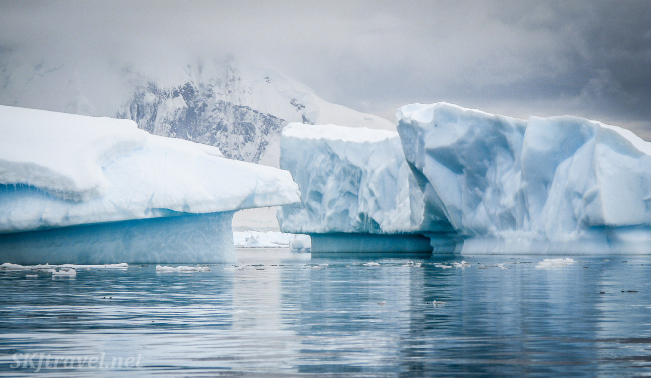 Kayaking among huge icebergs at Cuverville Island, Antarctica.