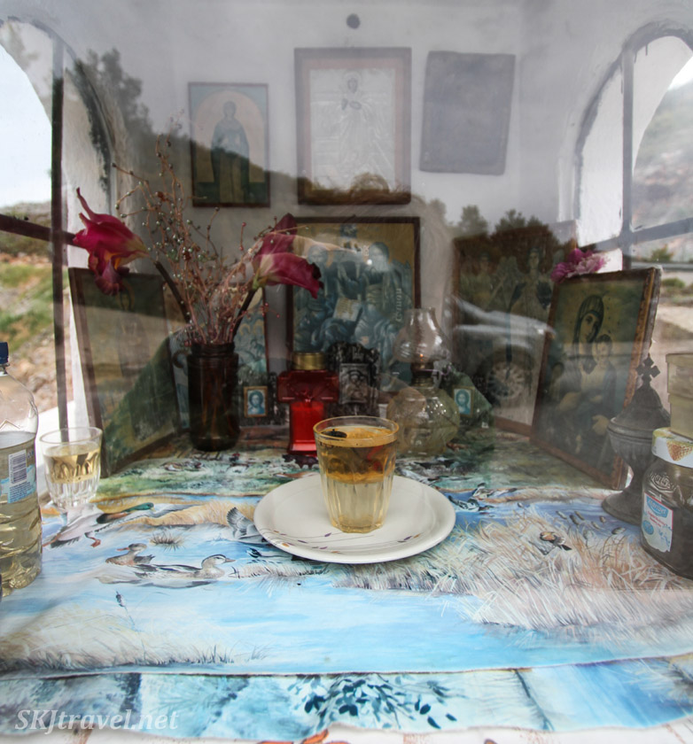 Interior space with offerings in roadside memorial shrine in the mountains of Chios Island, Greece.