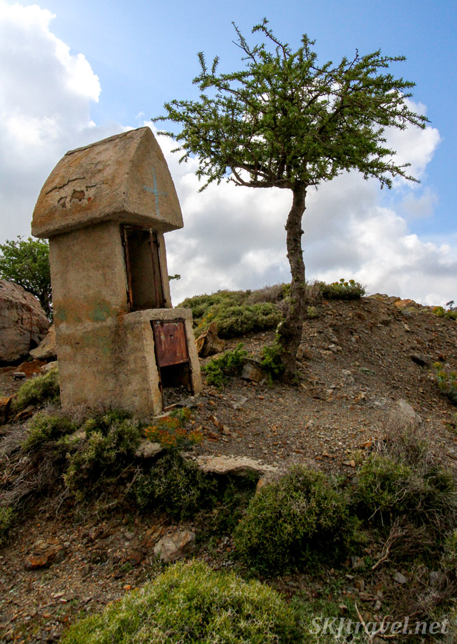 Old stone roadside shrine with lone tree in the mountains of Chios Island, Greece.