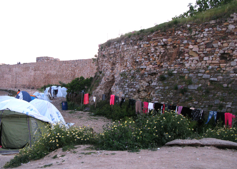 United Nations issued tents along the shore of Chios Island at the Souda refugee camp. A line of laundry again the city wall. April 2017.