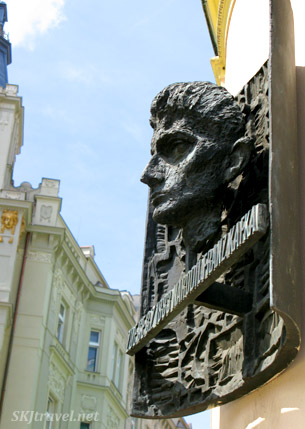 Bronze head of Franz Kafka on outside wall of building in Prague.