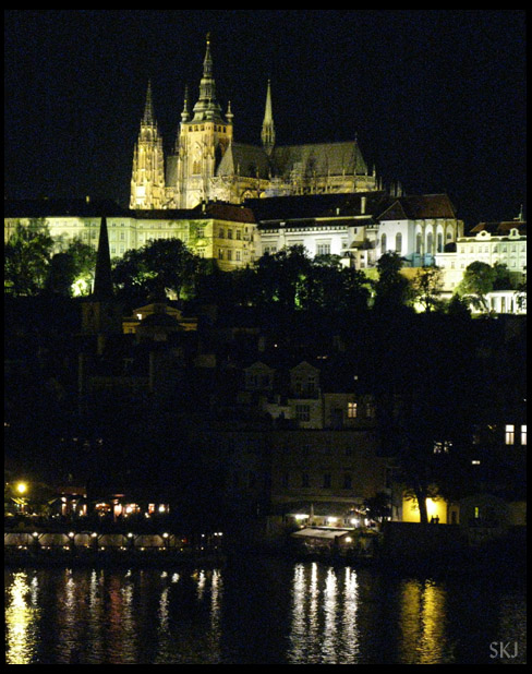 prague castle at night reflected in river