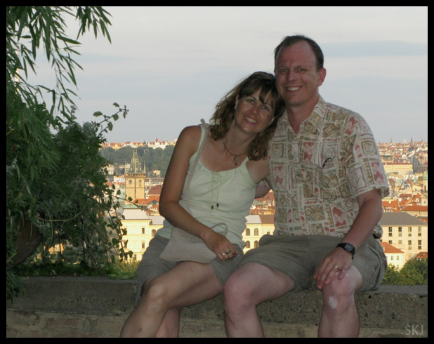 couple sitting on a low wall with city in background