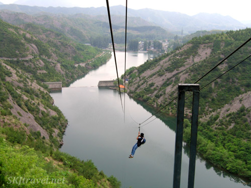 Zip line from the Great Wall down to a lake. China.
