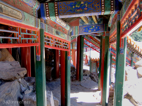 Colorful and chaotic walkways lead from one building to another through the rocks and forest. Summer Palace, China.