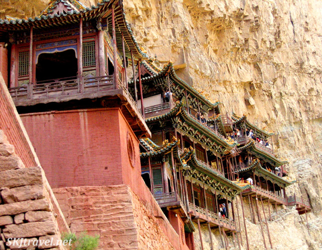 wooden buildings cling to a cliff side