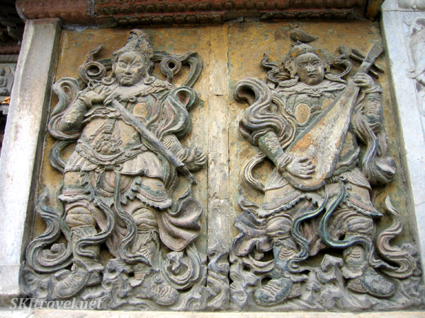 stone carving of 2 men with instruments