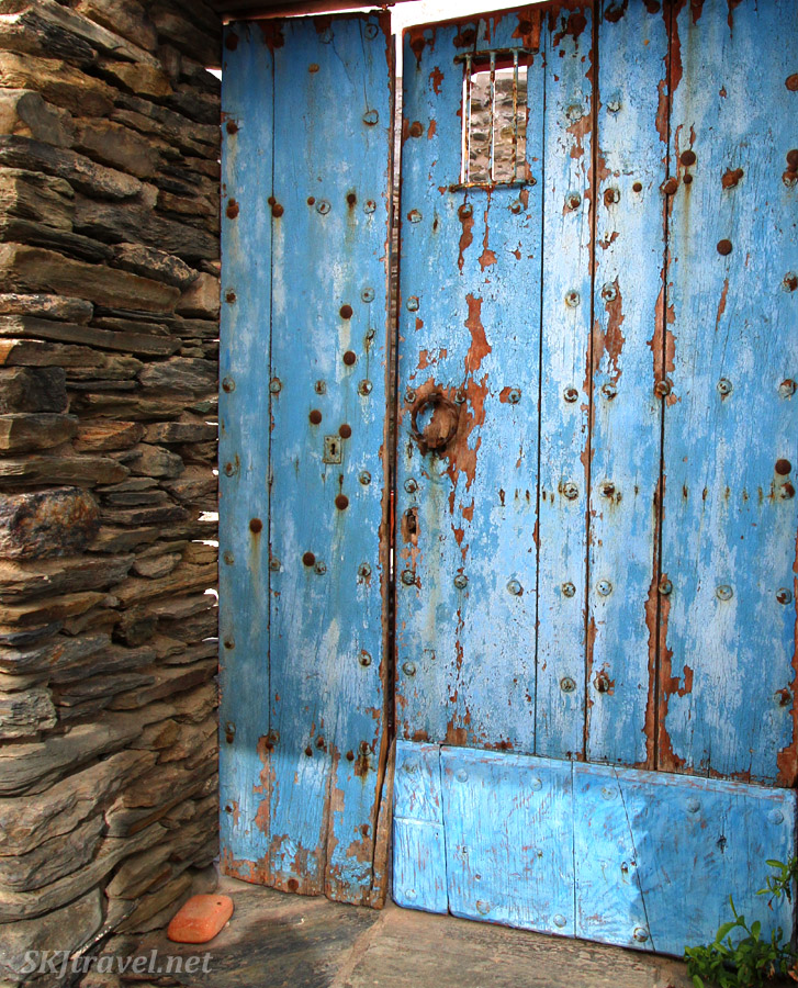 Old blue door in alley in Cadaques, Spain.