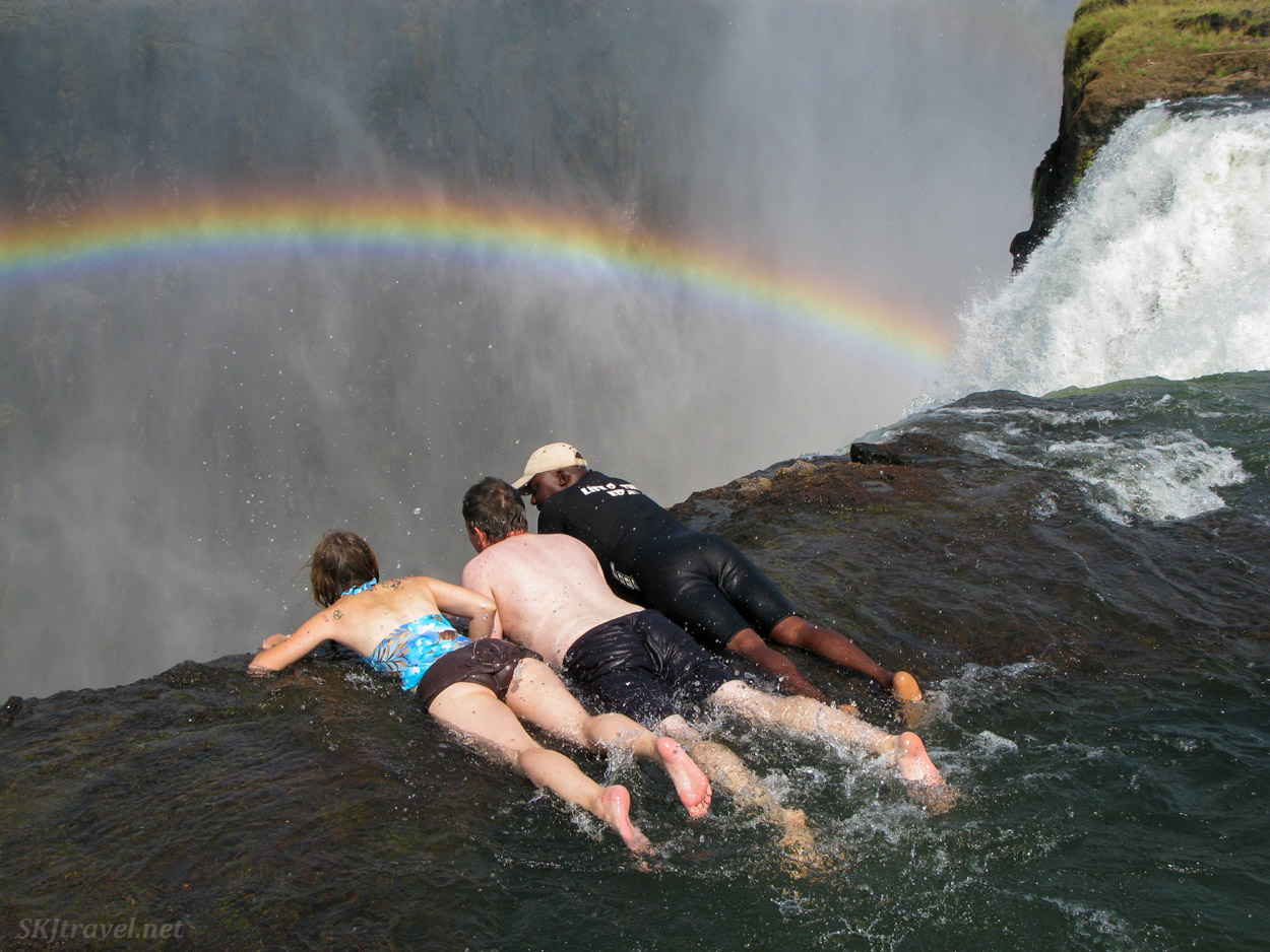 Shara and Erik peering over the edge of Victoria Falls, Zambia, at the Devil's Pool.