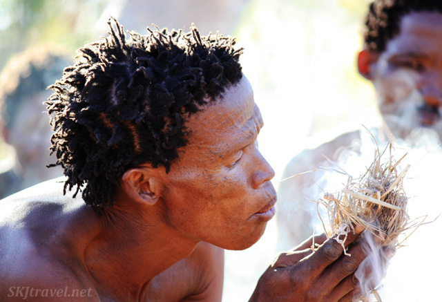 Man of the San bushmen tribe blowing smoldering kindling into a fire. Namibia.