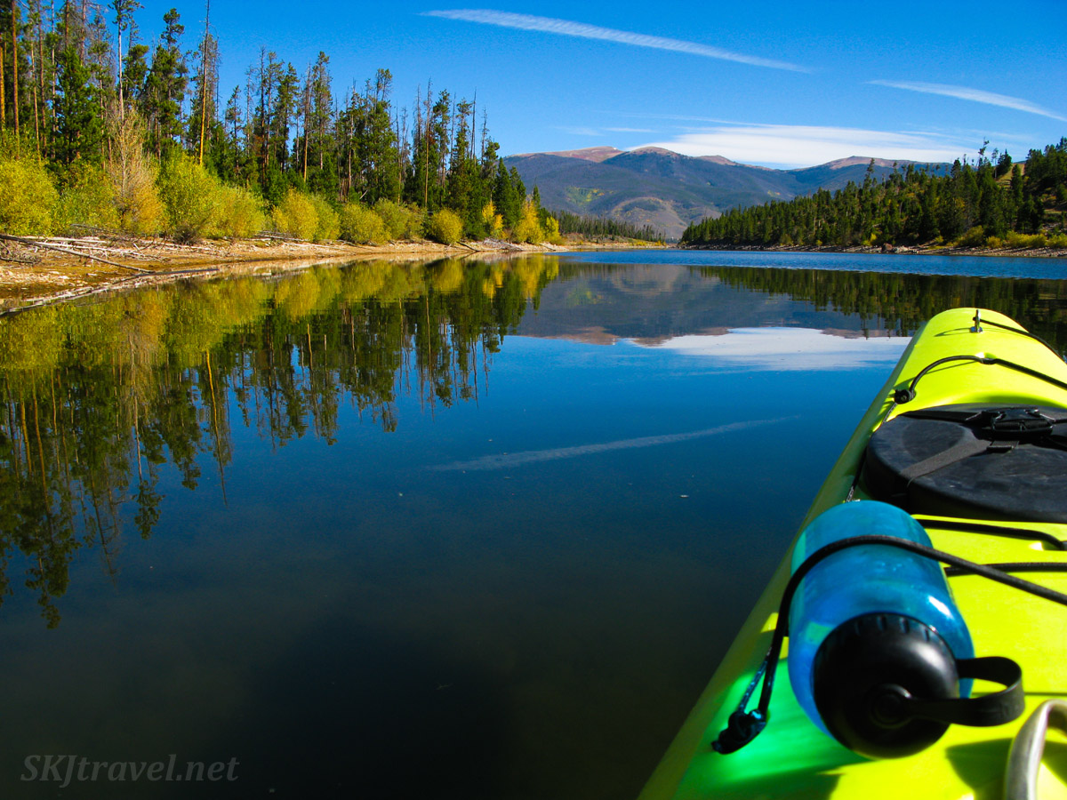 Kayaking on Lake Dillon, Colorado, in the autumn with glassy clear water reflecting the changes trees and bushes.