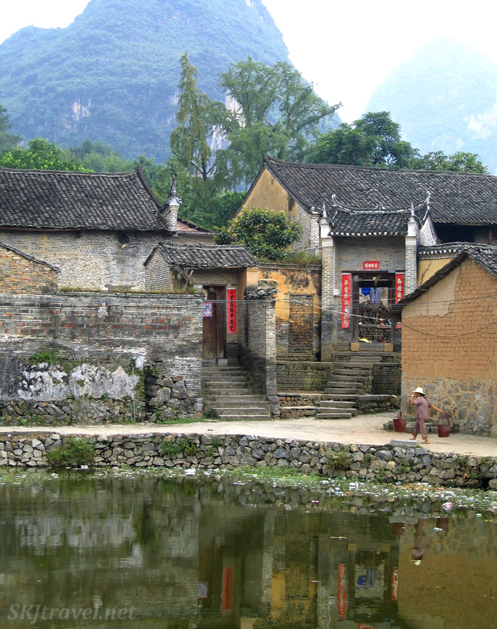 Woman carrying water home along the edge of man-made pond. Fuli, China.