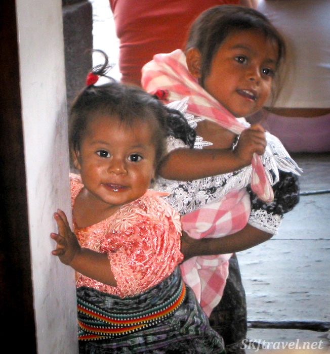 Two little girls peeking around a door frame in Antigua, Guatemala,  wearing traditional clothing.