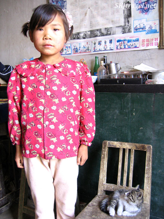 Young girl with her kitten inside her home in Dang Jiashan village, Shaanxi Province, China.
