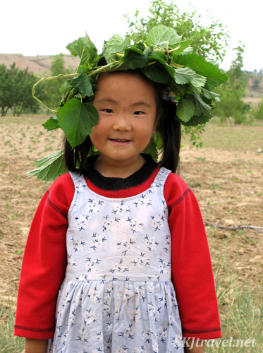 Kids making head wreathes out of mulberry bush branches. Dang Jiashan, China.