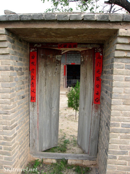 Entry doors into the temple courtyard at Dang Jiashan, China. Shrine for the lonely ancestor spirits directly in front.