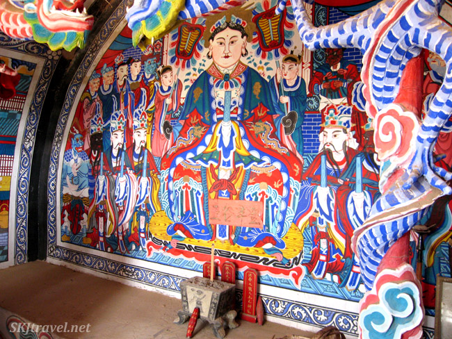 Offering shelf and main wall depicting the Holy Mother of the Ninth Heaven, village temple at Dang Jiashan, China.