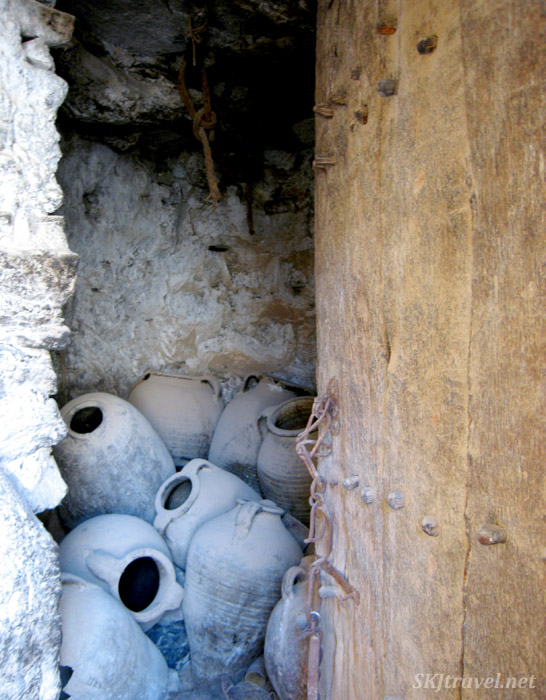 Several large stone amphorae stashed in a room, looking through the open wooden door, in a abandoned ksar in Douriet Tunisia. photo by Shara Johnson
