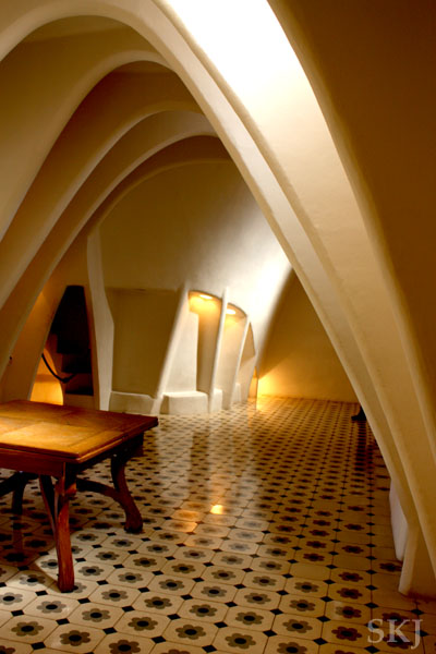 Attic space with closely-spaced white arches and black and white tiled floor in Batllo, Barcelona. photo by Shara Johnson
