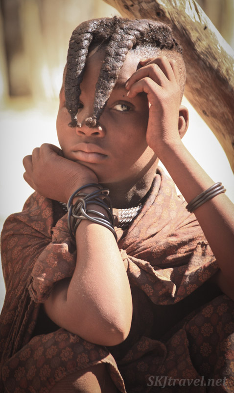 Young Himba girl with traditional hairstyle, thoughtful inside her kraal, Kaokoland, Namibia.