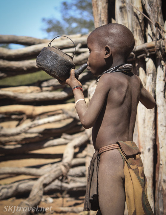 Himba child drinking water from an old rusted iron tea kettle. Kaokoland, Namibia.