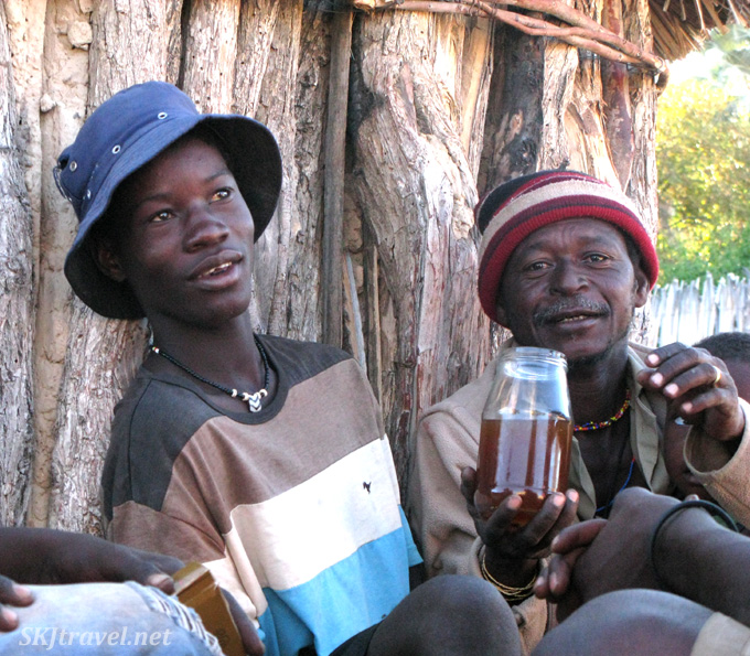 Men offering us homemade liquor outside a hut in a non-traditional village near Epupa Falls, Kaokoland, Namibia.