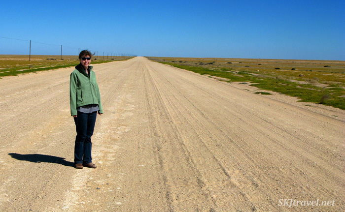Shara stands in the middle of a perfectly flat road stretching across Namibia.