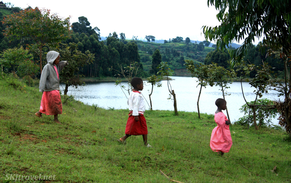 Three girls walking to school on the shore of Lake Bunyoni, Uganda.