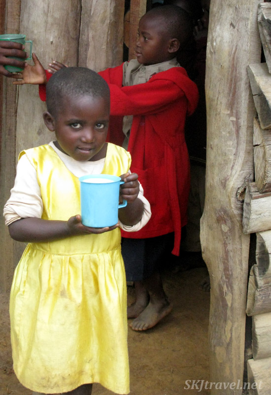 Adorable little girl receiving a cup of porridge at primary school, Lake Bunyoni, Uganda.