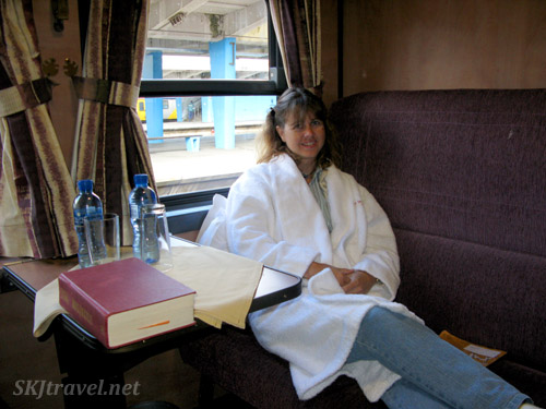 girl in bathrobe sitting on train bench