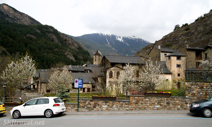 Typical street in an Andorran town. Spring flowering trees and signature stone buildings.