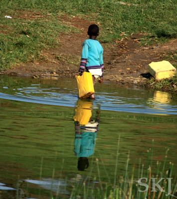 Small child collects water in a plastic container. Kazing Channel in Queen Elizabeth National Park, Uganda.