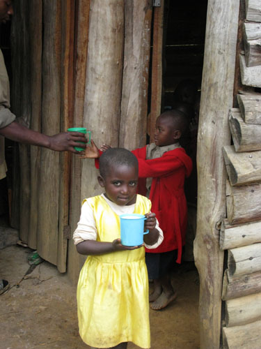 Young child receiving porridge at primary school on Lake Bunyoni, Uganda